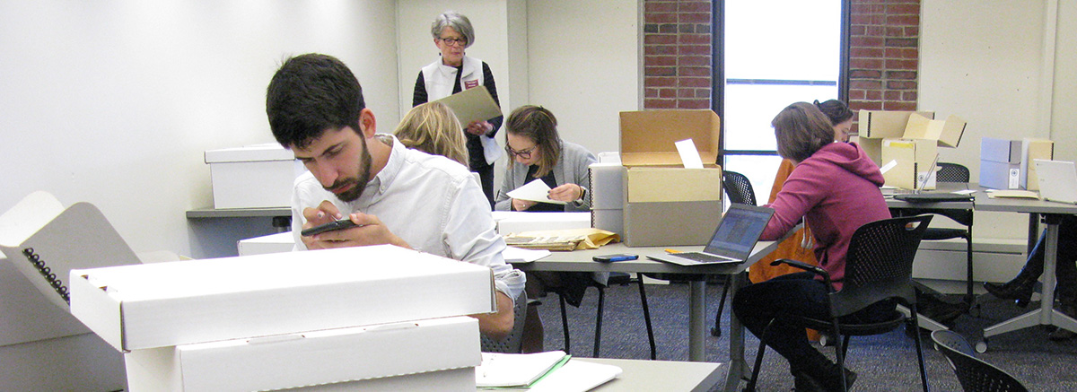 Graduate students working with archival materials in the UMass Special Collections and Archives.