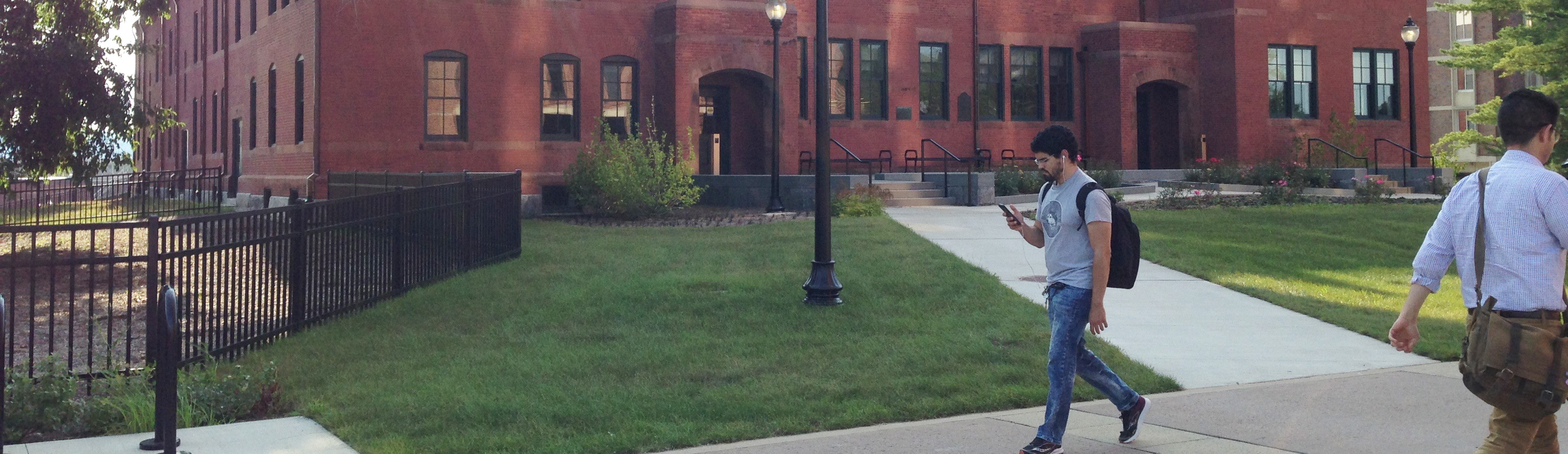 A student wearing a backpack walks past the South College building.