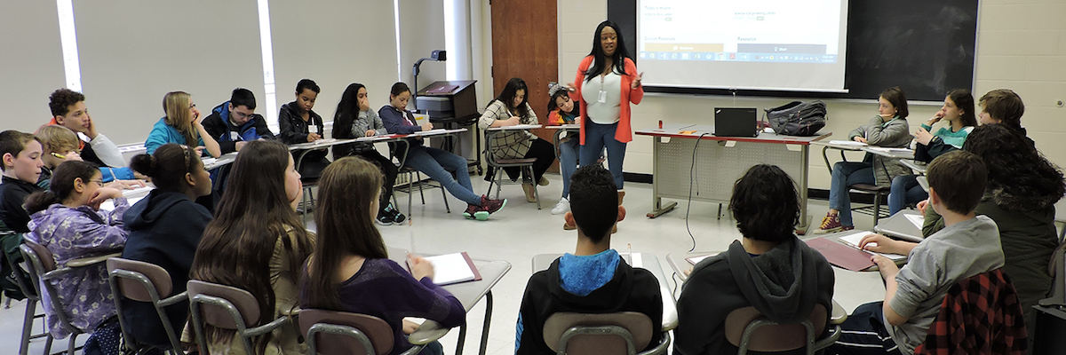 A teaching workshop. Participants sit in a circle, a woman speaks standing in front of a PowerPoint presentation