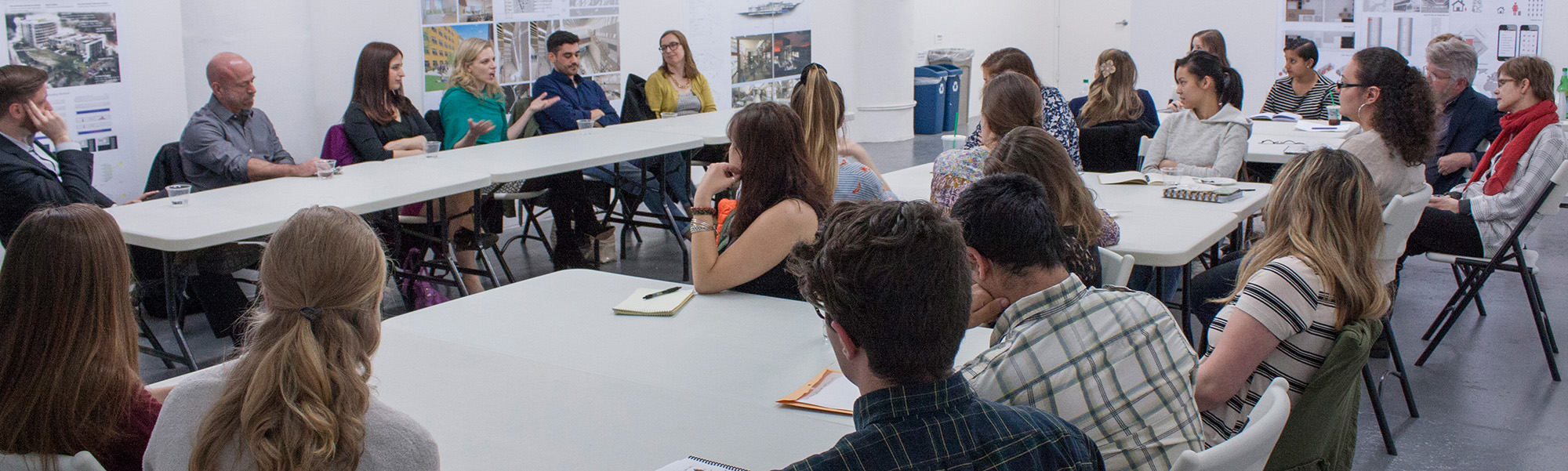 A panel of alumni take questions from UMass English majors in a large airy loft space in New York City.