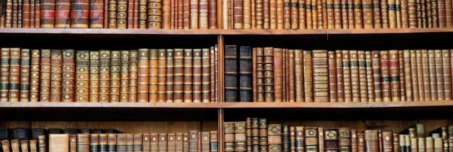 closeup of old books on shelves.