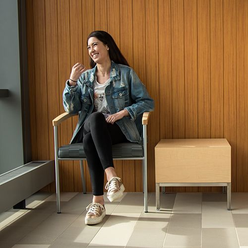 Dani Perez sitting in the sunny lobby of South College, laughing as she glances out the window.