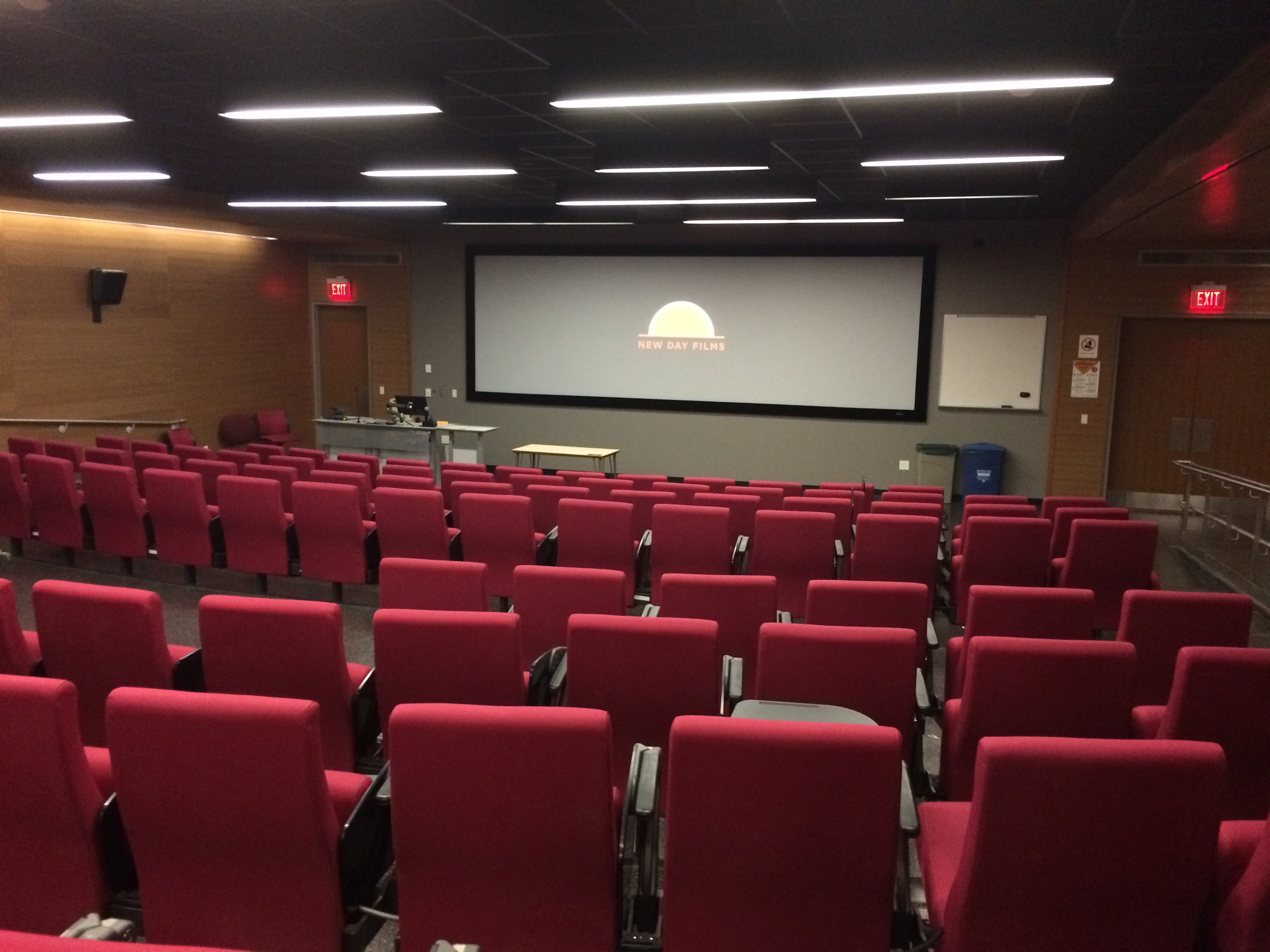 Large empty lecture hall with a screen in front. A sunset is displayed.