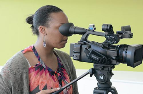 A student records video with a camera.