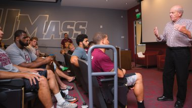 Paul Wennik '62 speaks to UMass Amherst Football players
