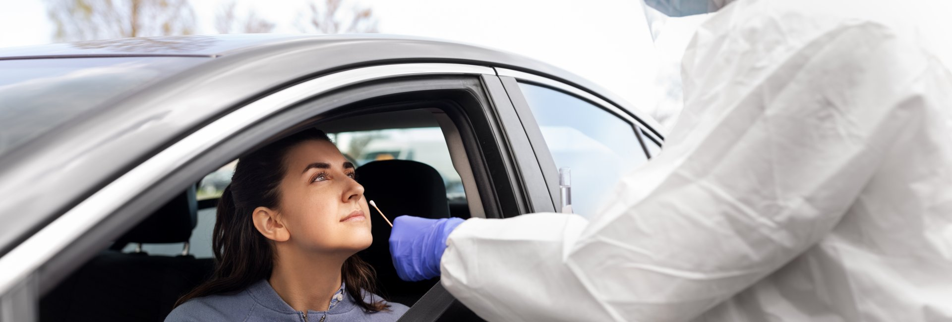 Woman in car with healthcare worker adminstering COVID-19 nasal swab test