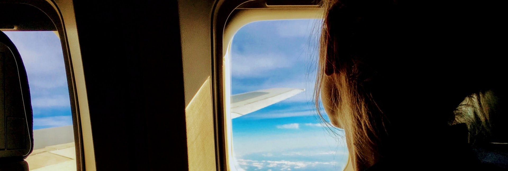 A girl looking out a plane window