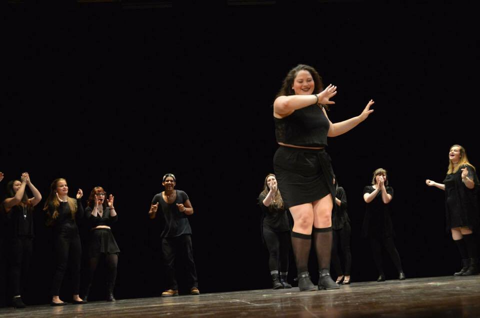 A student dances in Nostras Voces while other performers look on.