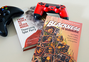 Two of Russworm's books are pictured with game controllers.