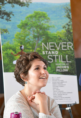 A woman poses in front of a poster reading 'Never Stand Still'