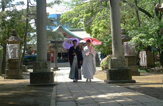 two women in kimono walk together with parasols