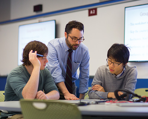 Two students listen attentively as a professor lectures between them.