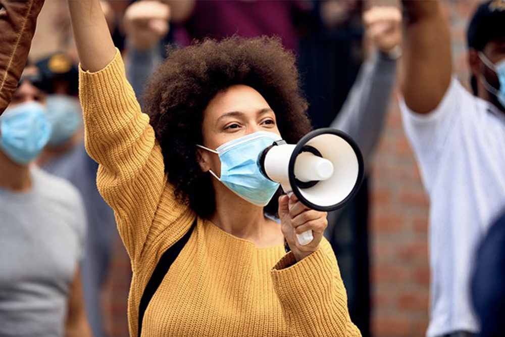 A young Black woman wearing a protective mask and holding a megaphone.