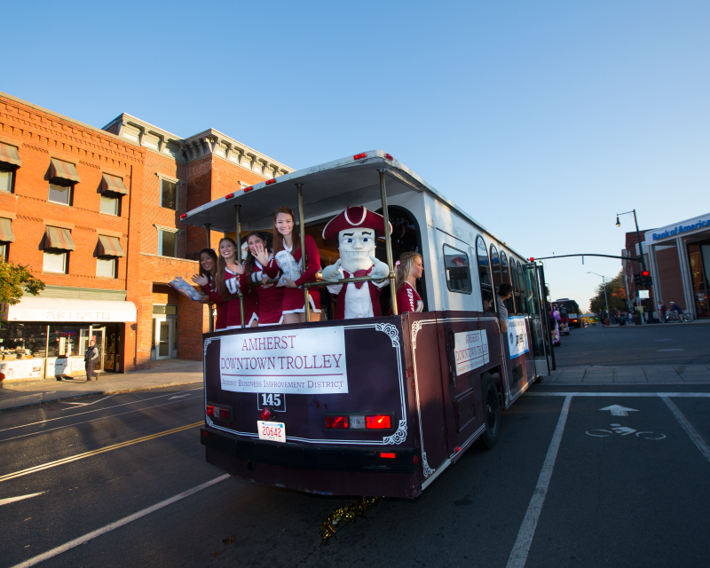 Sam the Minuteman rides the trolley into Downtown Amherst.