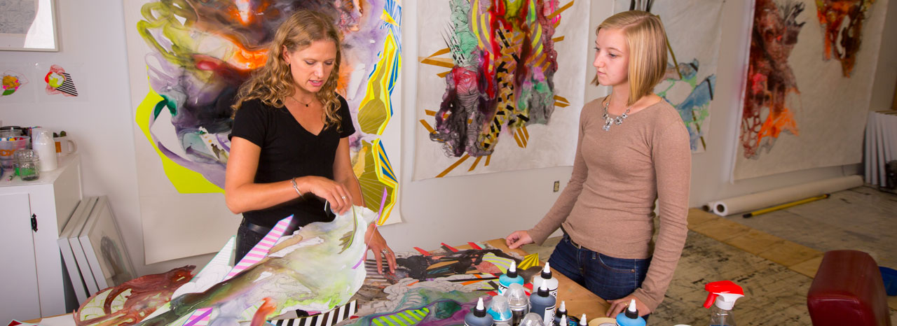 A student assists an artist in her studio.