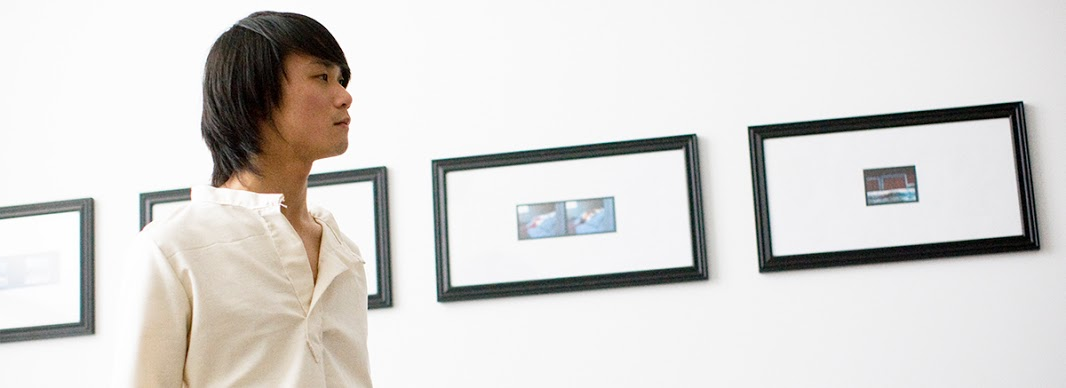 A student looks at framed paintings