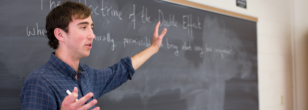 A student points to a blackboard on which is written