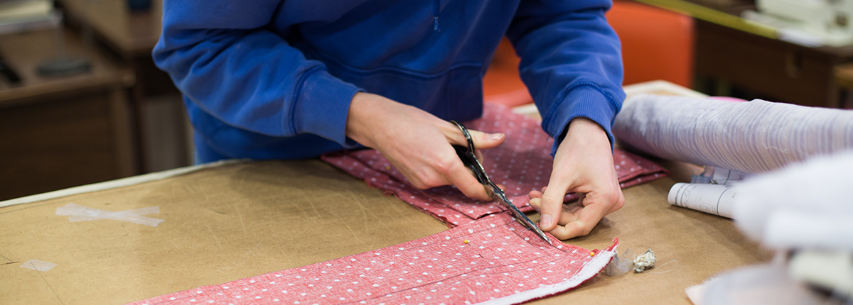 Hands cutting fabric into square sections.