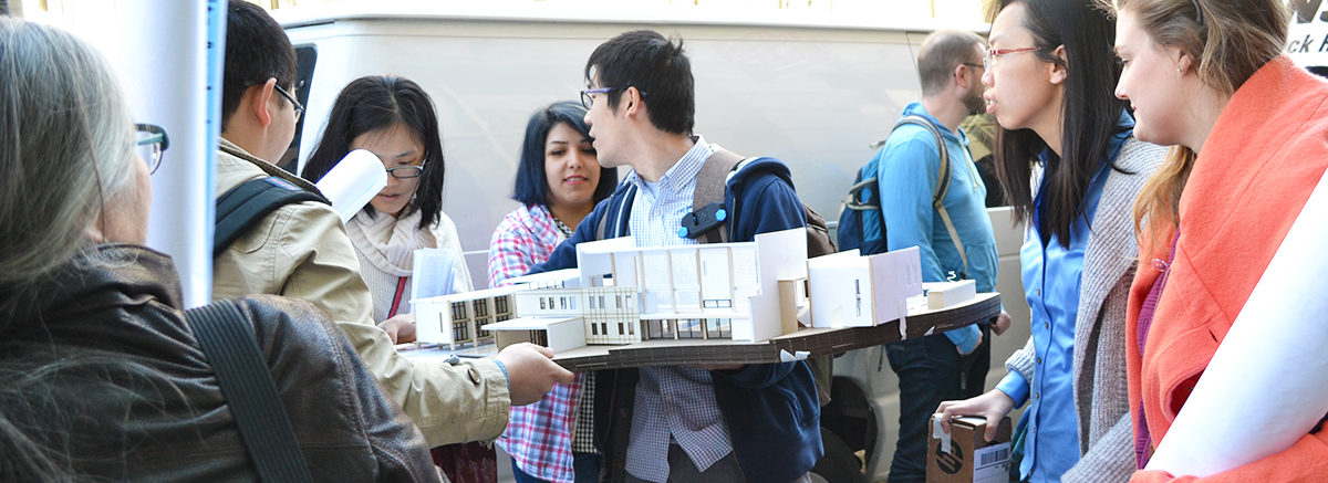 Students look at architectural models in a display space