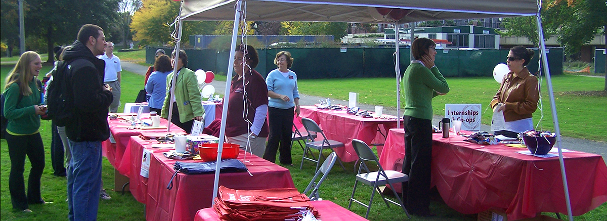 Students staff tables at an outdoor career fair on campus