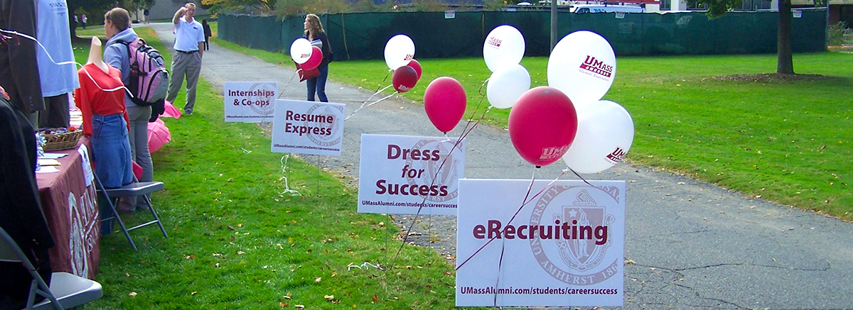 Signs and balloons decorate tents at an outdoor Career Fair.