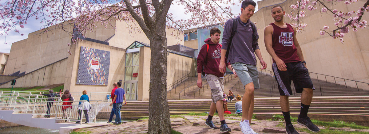 Three students walk behind the UMass Amherst Fine Arts Center.