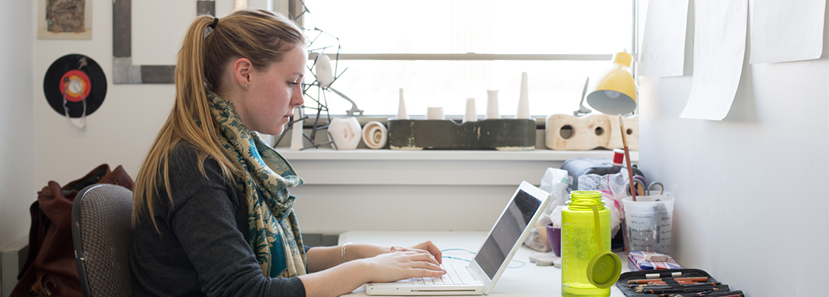 A student works in her dorm room