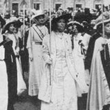 black and white picture from the beginning of the 20th century shows women in white dresses marching.