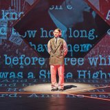 An actor stands alone on a stage covered with projected words