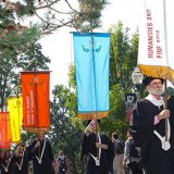 Faculty members in caps and gowns march with banners.