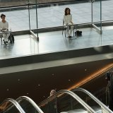 Art performance paying homage to city office workers. Individuals sit at desks between the cubicle-like glass partitions of Brookfield Place's atrium, in downtown Manhattan