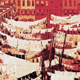a red tinted view of a street with clotheslines of laundry stretching across it.