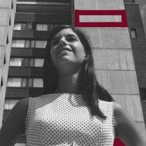 A young woman photographed from below, stands in front of one of the Southwest towers on the campus of UMass Amherst. Architectural features of the building are outlined in red.