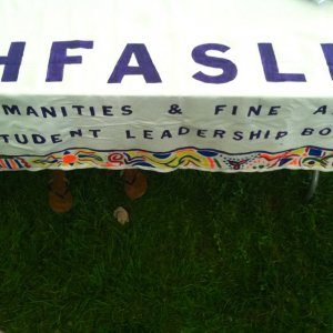The Humanities and Fine Arts Student Leadership Board (HFASLB) banner draped over a table