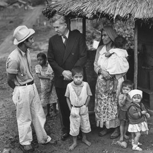 Man in suit speaks with a family in Mexico
