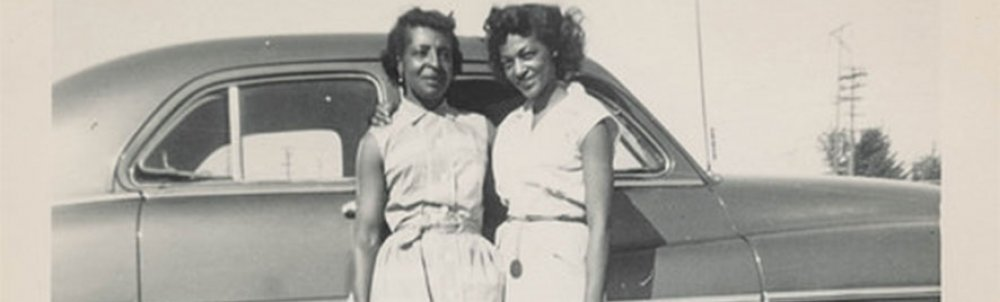 A black and white photograph of two black women standing in front of a car