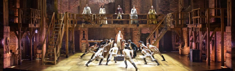 Picture of actors on stage from the musical Hamilton