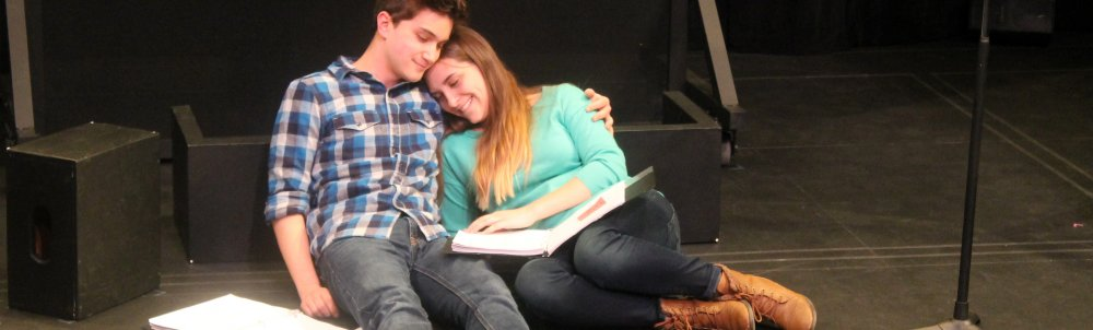 Two student actors pose on stage with scripts.