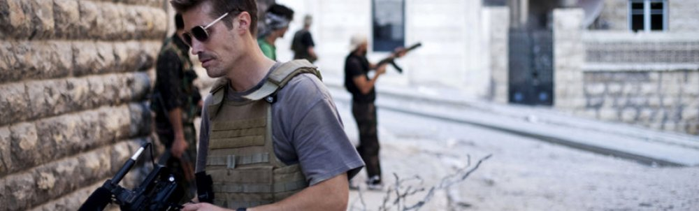 James Foley shown holding a video camera. Behind him, men brandish guns.