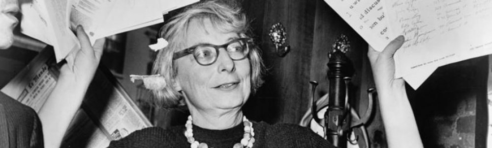 Jane Jacobs, shown holding papers in a black and white photo.