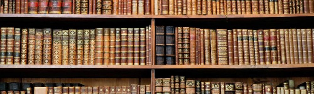 An image of leather-bound books on shelves.
