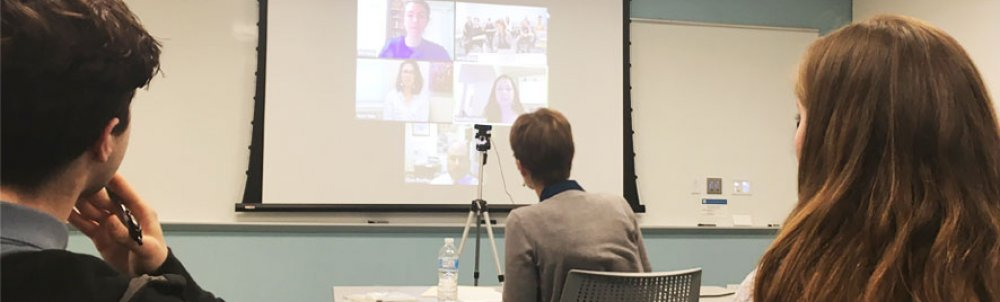 Students view a screen on which five alumni are projected.