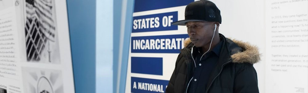 A man wearing earbuds stops in front of the States of Incarceration exhibit