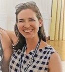 Photo of Alison Russell, who has pale skin and straight brown hair and is wearing a plaid top.