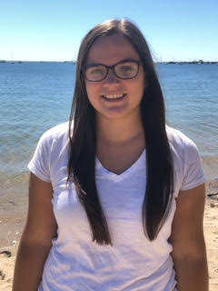 Photo of Alison Smith, who has pale skin and straight brown hair. She's wearing glasses and a white top.