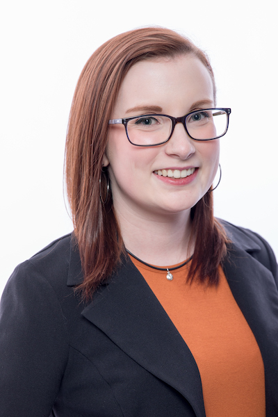 Tianna has fair skin and shoulder-length red hair. She is wearing a black blazer and is against a white background.