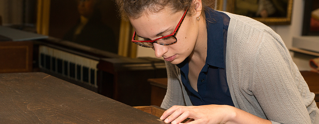 Student working with antique furniture