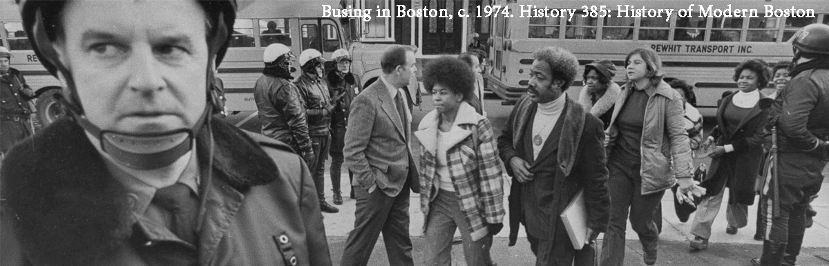 historical image of busing in Boston. White police officer with a group of predominantly African American adults and students walking, school bus in background