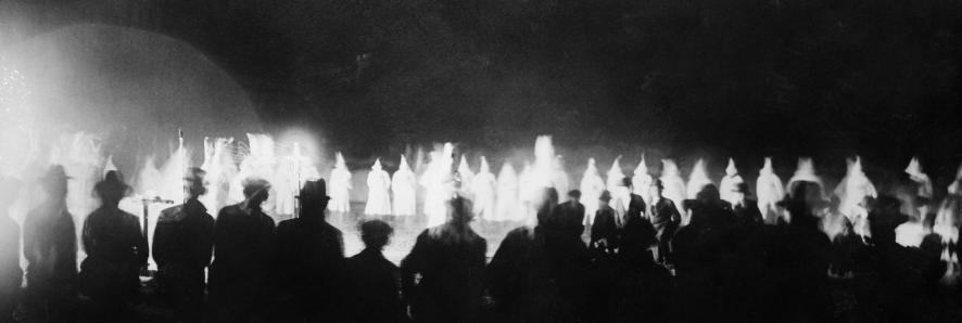 Onlookers watch as the Ku Klux Klan initiates new members at a Miami golf course in the 1920s. Bettmann / Getty Images