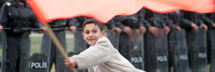 Young boy holding a red flag